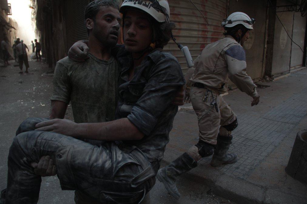 A volunteer carries his injured teammate