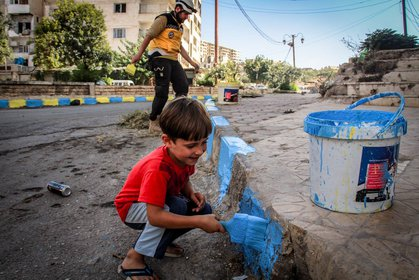 Children help volunteers rehabilitate a neighbourhood